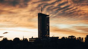 3840x2160 Wallpaper building, apartments, silhouette, sunset, river