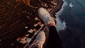 3840x2160 Wallpaper legs, sneakers, city, aerial view, coast, mountains