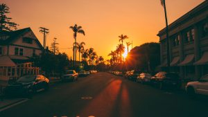 3840x2160 Wallpaper street, sunset, palm trees, road, road signs, cars